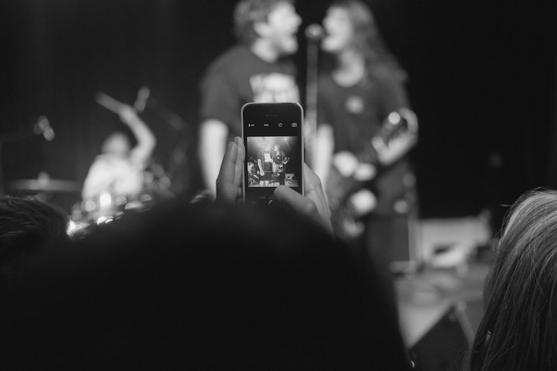 a person holding a phone at a performance