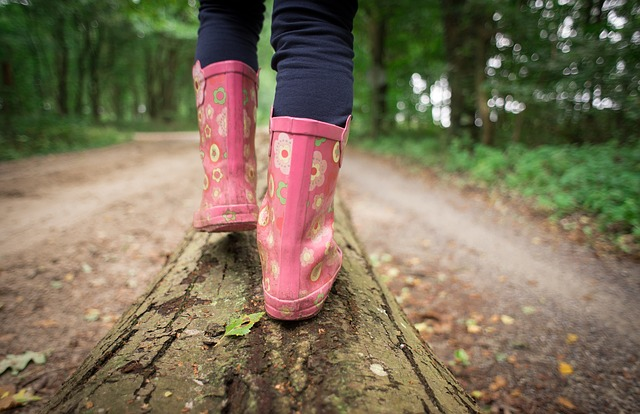 a girl walking on a log in the woods wearing pink boots