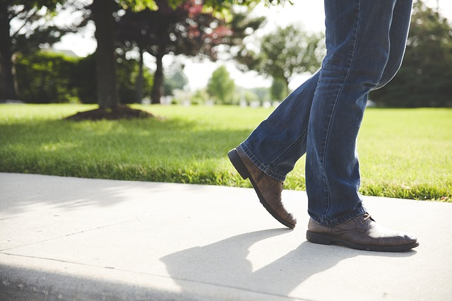 a man walking outside in a park on a paved path