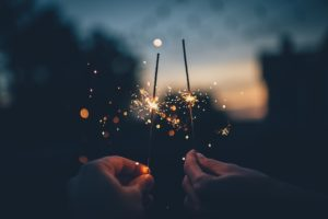 two people holding sparklers