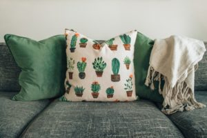 Home decor couch with fall themed pillow.