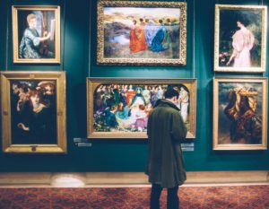 Man looking at paintings in a museum.