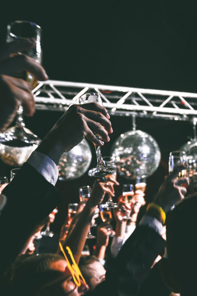 People raising their champagne glasses up.