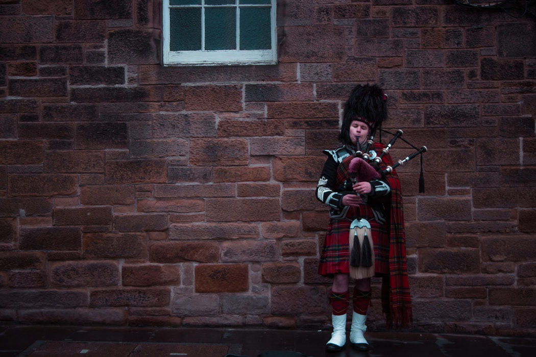 A man playing bagpipes against a wall.